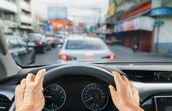 驾驶在交通堵塞的资深妇女一辆汽车 库存照片