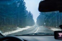 驾驶在冬天路的一辆汽车在飞雪 库存图片