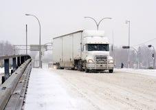 驾驶在冬天雪风暴的半拖车 免版税库存照片