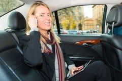 驾驶在出租汽车的妇女,她是在电话 免版税库存照片