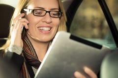 驾驶在出租汽车的年轻女实业家,她使用片剂计算机a 免版税库存图片