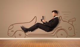 驾驶在墙壁上的愉快的人一辆手拉的汽车 免版税库存照片