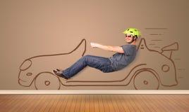 驾驶在墙壁上的愉快的人一辆手拉的汽车 免版税图库摄影