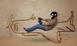 驾驶在墙壁上的滑稽的飞行员一架手拉的飞机 库存图片