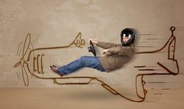 驾驶在墙壁上的滑稽的飞行员一架手拉的飞机 免版税图库摄影