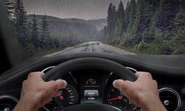 驾驶在多雨天气 从司机角度的看法,当在轮子时的手 雨飞溅的挡风玻璃 免版税图库摄影