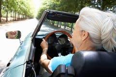 驾驶在她的跑车的高级妇女 免版税库存图片