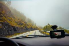 驾驶在山有薄雾的路的一辆汽车 免版税库存图片