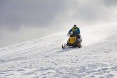 驾驶在山的一个人体育雪上电车 库存照片