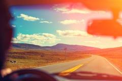 驾驶在山路的一辆汽车在日落 免版税库存照片