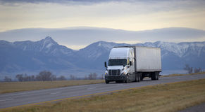 驾驶在山高速公路的半卡车 免版税库存照片