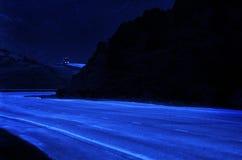 驾驶在弯曲的小山的晚上的卡车 免版税库存照片
