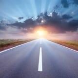 驾驶在往朝阳的一条空的路 免版税库存照片