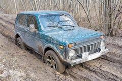 在森林公路的俄国做的SUV 免版税库存照片