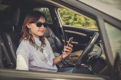驾驶在愉快的亚裔妇女一辆汽车 免版税库存照片