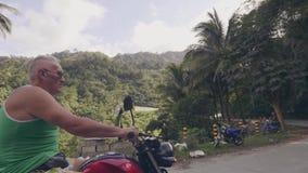 驾驶在摩托车的成人人在青山的乡下路盖了热带乘坐森林旅行的人  股票视频