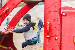 驾驶在操场的男孩一辆玩具汽车 免版税图库摄影