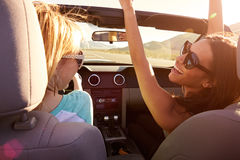 驾驶在敞篷车汽车的旅行的两个女性朋友 免版税库存照片