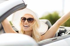 驾驶在敞蓬车汽车的愉快的妇女 免版税库存照片