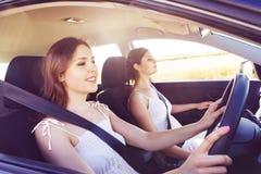 驾驶在旅行的两名妇女一辆汽车 免版税图库摄影