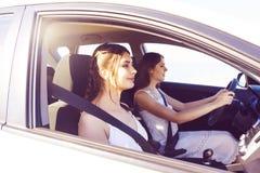 驾驶在旅行的两名妇女一辆汽车 免版税库存图片