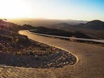 驾驶在旅行的越野汽车通过被铺的适当的块弯曲了在干沙漠和岩石山风景中的路 库存图片