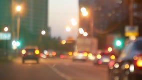驾驶在晚上 在城市观看挡风玻璃和被弄脏的汽车 前面汽车的窗口有被弄脏的城市交通的 股票录像