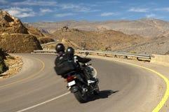 驾驶在曲线的一辆摩托车的游人 图库摄影