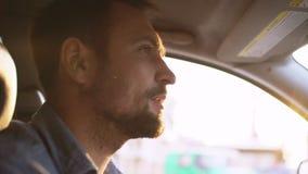 驾驶在有太阳火光开窗口的城市的英俊的有胡子的人 影视素材