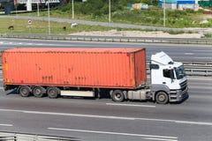 驾驶在有橙色容器的高速公路的半拖车 免版税库存照片