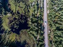 驾驶在有湖的路不尽的杉树森林的美丽的加拿大露营车公共汽车停泊土地鸟瞰图旅行背景 免版税图库摄影