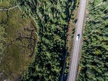 驾驶在有湖的路不尽的杉树森林的美丽的加拿大露营车公共汽车停泊土地鸟瞰图旅行背景 库存照片