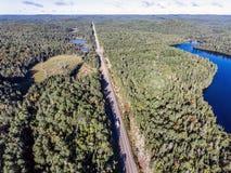驾驶在有湖的路不尽的杉树森林的美丽的加拿大露营车公共汽车停泊土地鸟瞰图旅行背景 免版税库存图片