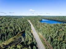 驾驶在有湖的路不尽的杉树森林的美丽的加拿大露营车公共汽车停泊土地鸟瞰图旅行背景 免版税库存照片