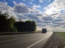 驾驶在柏油路农村风景的卡车 库存照片