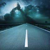驾驶在柏油路往近来风雨如磐的夜 库存照片