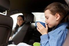 驾驶在汽车和喝从杯子的小女孩 免版税库存照片