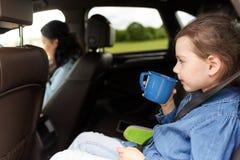 驾驶在汽车和喝从杯子的小女孩 图库摄影