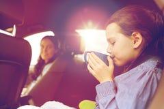 驾驶在汽车和喝从杯子的小女孩 库存图片