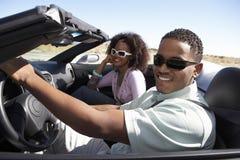 驾驶在沙漠路的夫妇敞篷车 免版税库存照片
