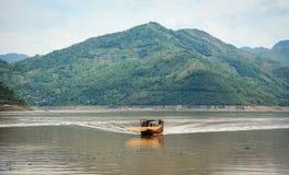 驾驶在河的一条木小船 免版税库存图片