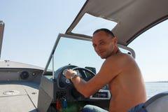 驾驶在河的上尉一条小船 库存照片