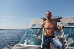 驾驶在河的上尉一条小船 库存图片