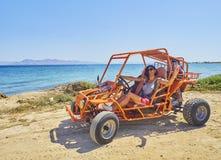 驾驶在海滩沙丘的一个愉快的女孩一个儿童车 海滩睡椅希腊海岛kefalos kos桔子伞 南 免版税库存照片