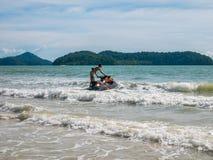 驾驶在海滩的一个人一只快艇 库存照片
