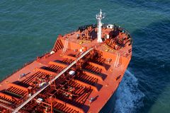 驾驶在深蓝色海洋的大红色货船 免版税库存图片