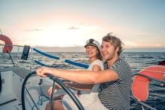 驾驶在游艇的年轻夫妇 库存照片