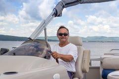驾驶在湖的成熟人一条浮船小船 图库摄影