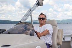 驾驶在湖的成熟人一条浮船小船 免版税库存图片