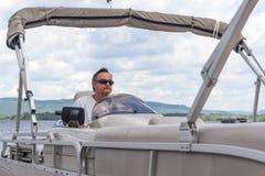 驾驶在湖的成熟人一条浮船小船 库存照片
